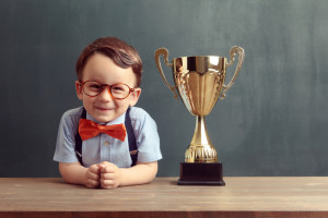 A cute, smiling 2-3 years old boy is standing behind a wooden table with a golden trophy on it. Little boy is wearing an orange bow tie, red glasses and blue trousers with suspenders.
